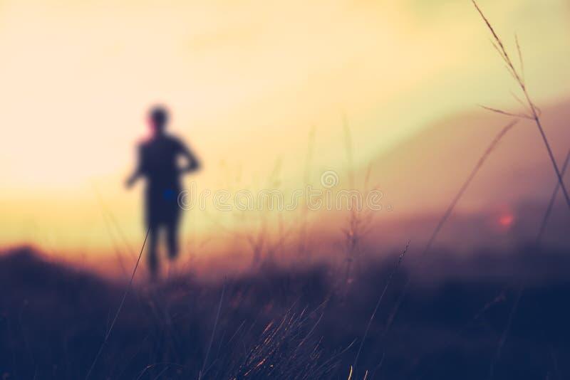 在日落的小山赛跑者 库存图片