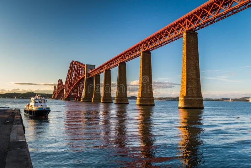在日落的小船在一座老金属桥梁在苏格兰 免版税库存图片