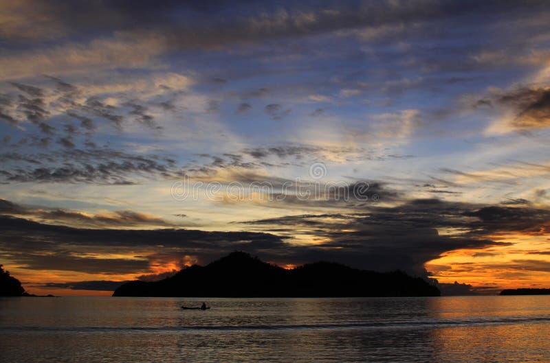 在日落的小船在海岛和云彩后 免版税库存照片