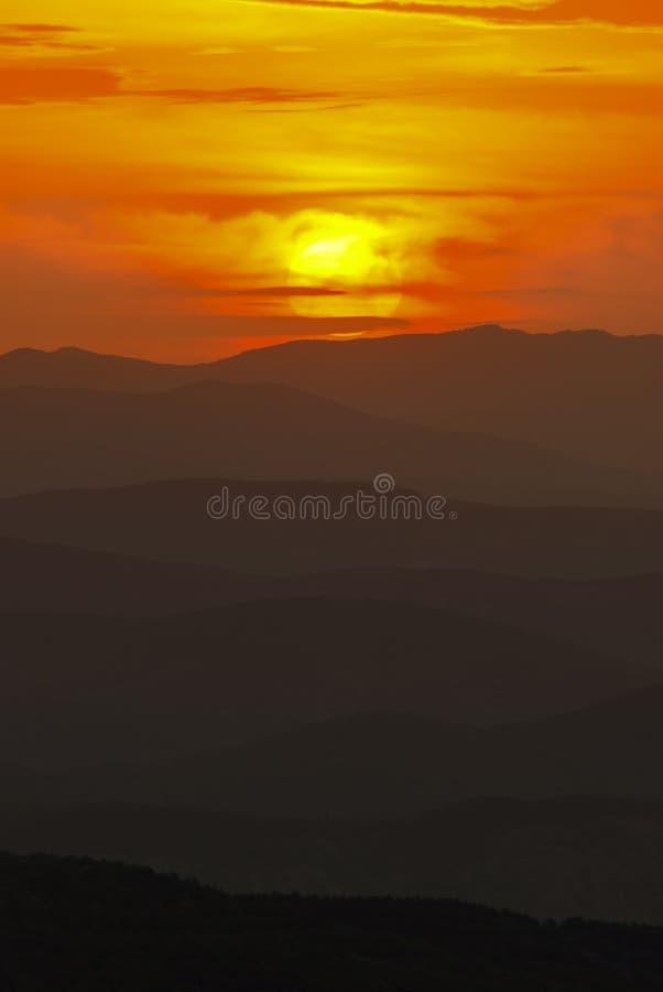 在日落的山横向 从山峰的惊人的看法在岩石、低云、蓝天和海在晚上 五颜六色 免版税库存图片
