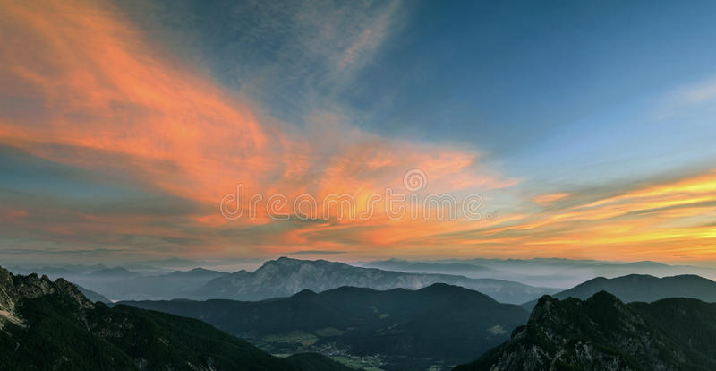 在日落的山风景在朱利安阿尔卑斯山 在五颜六色的云彩和层状山的惊人的看法 库存照片