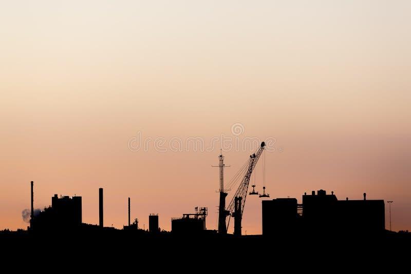 在日落的工厂厂房剪影 免版税库存图片