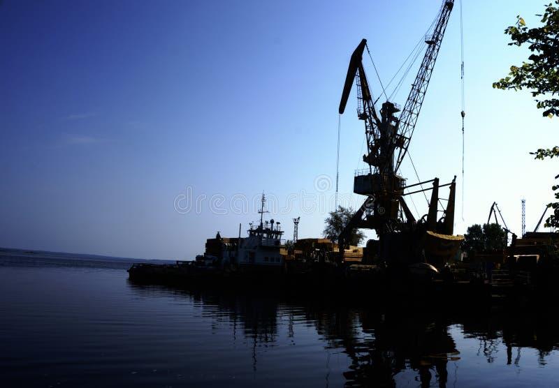在日落的巨大的起重机 端口船 免版税图库摄影
