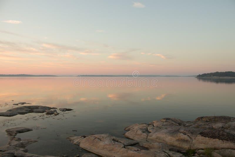 在日落的平安的斯堪的纳维亚海岸线 图库摄影