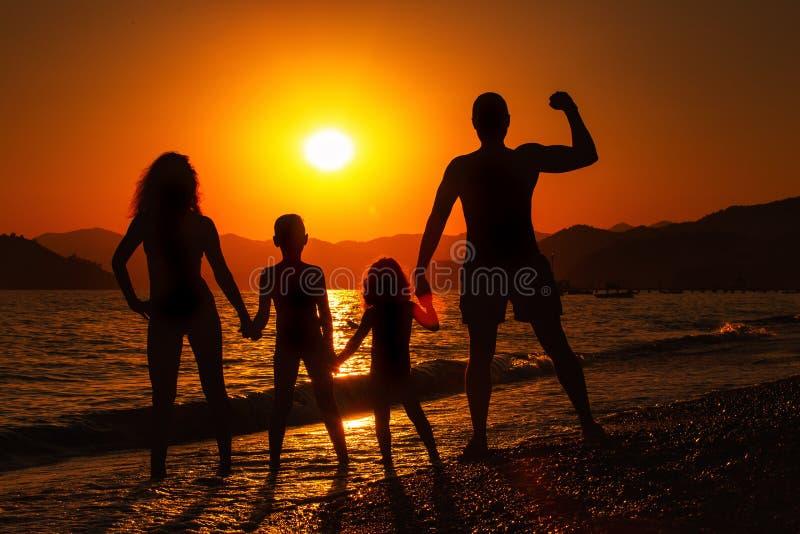 在日落的幸福家庭剪影 库存图片