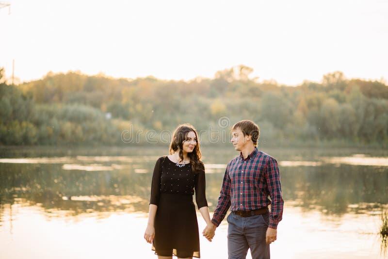 在日落的愉快的夫妇在河附近 爱,青年时期,幸福 免版税库存图片