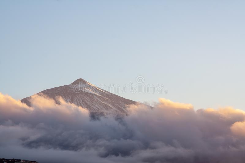 在日落的斯诺伊山与被覆盖的云彩 免版税库存照片