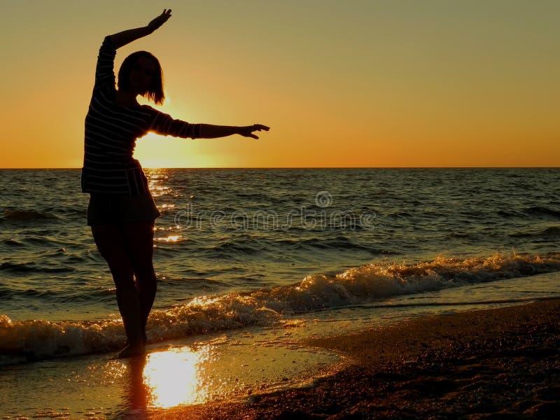 在日落的无忧无虑的妇女跳舞在海滩 图库摄影