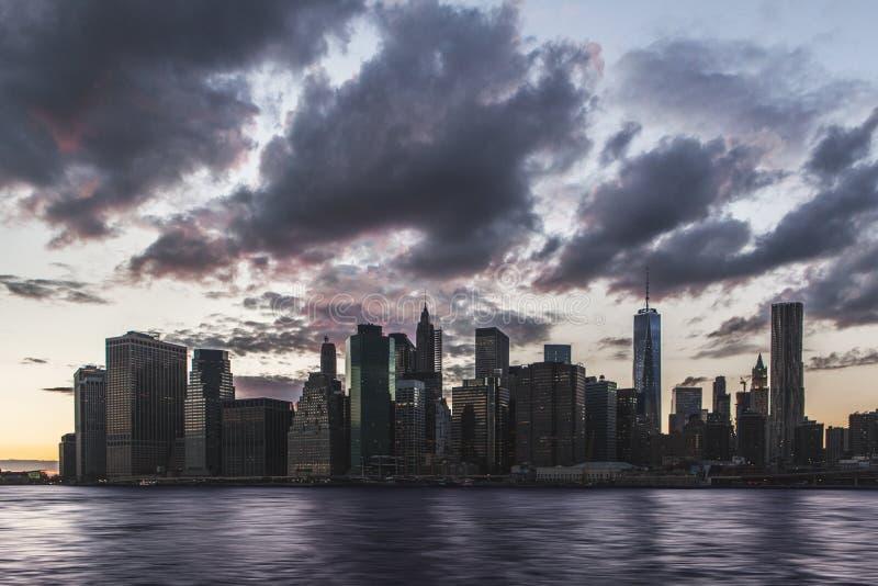 在日落的曼哈顿地平线与在天空的云彩 免版税库存照片