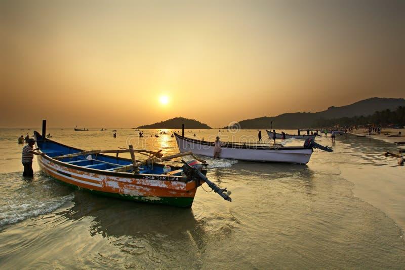 在日落的果阿海滩与传统渔船Palolem Agonda 库存照片