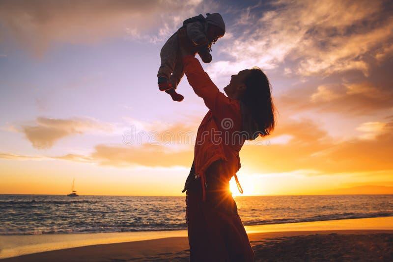 在日落的母亲和婴孩剪影在海靠岸 库存照片