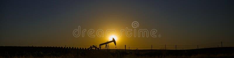 在日落的油泵剪影 免版税图库摄影