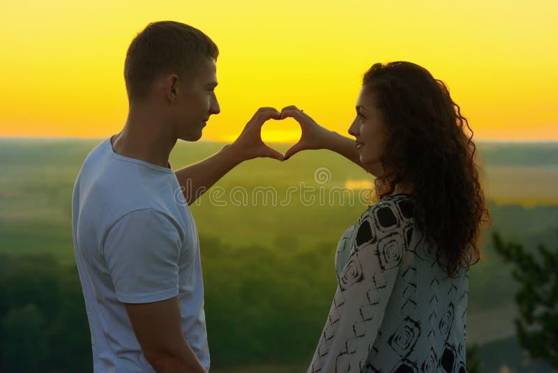 在日落的浪漫夫妇显示从手、美好的风景和明亮的黄色天空,爱柔软概念的心脏形状,年轻 库存图片