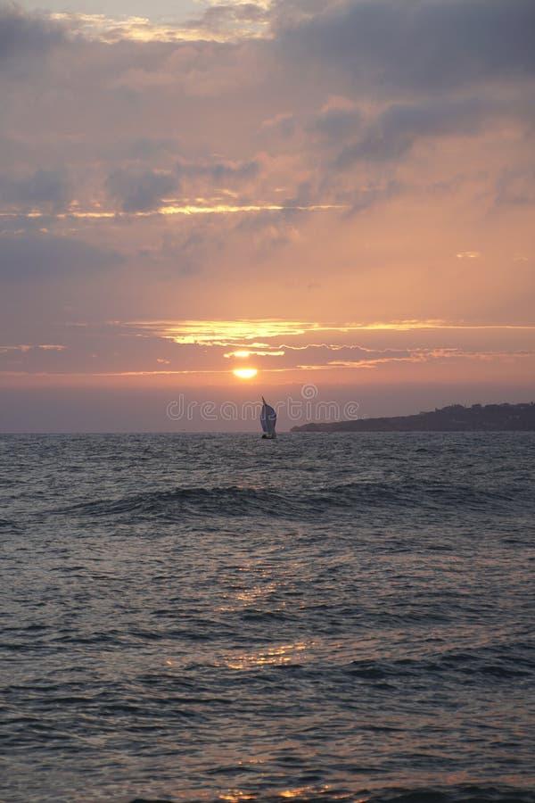 在日落的海洋 atlantes 晚上天际 橙色天空和波浪表面上 库存图片
