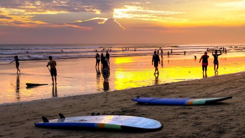 在日落的海滩男孩运载的longboard在kuta,巴厘岛 免版税库存照片