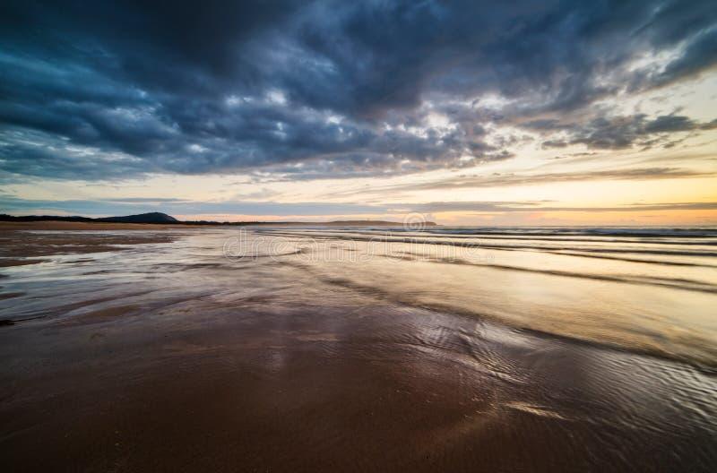 在日落的海滩在一风暴日 免版税库存照片