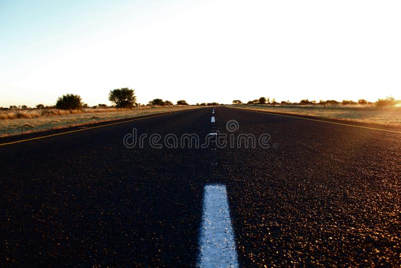 在日落的涂焦油路 免版税图库摄影