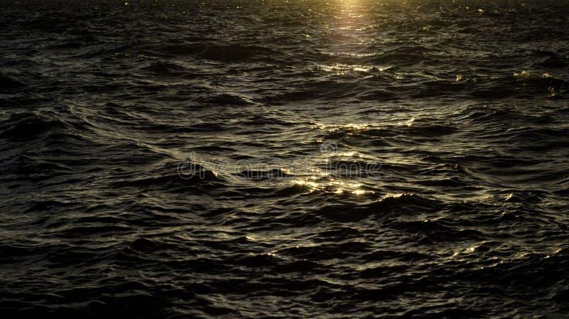 在日落的深黑暗的水与波浪 免版税库存照片