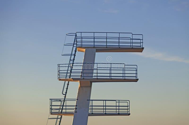 在日落的游泳的跳跃的塔 免版税库存照片