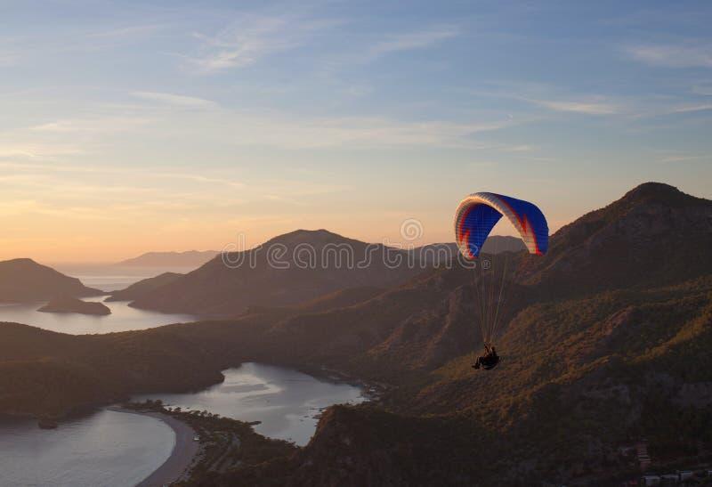 在日落的滑翔伞飞行在Oludeniz,土耳其 免版税库存照片