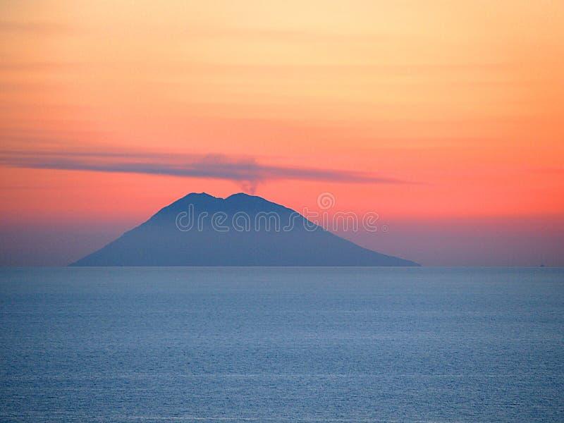 在日落的火山斯特龙博利岛在蓝色海 图库摄影