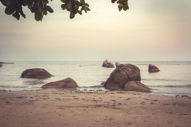 在日落的热带沙滩与在水和垂悬的大岩石离开在海浪期间在温暖的颜色在葡萄酒样式 免版税图库摄影