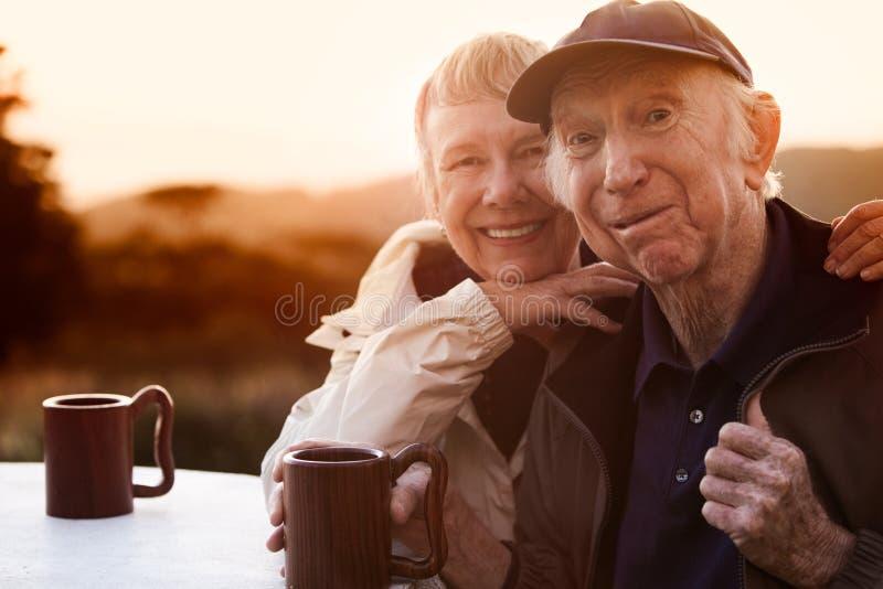 在日落的爱恋的高级夫妇 免版税库存照片