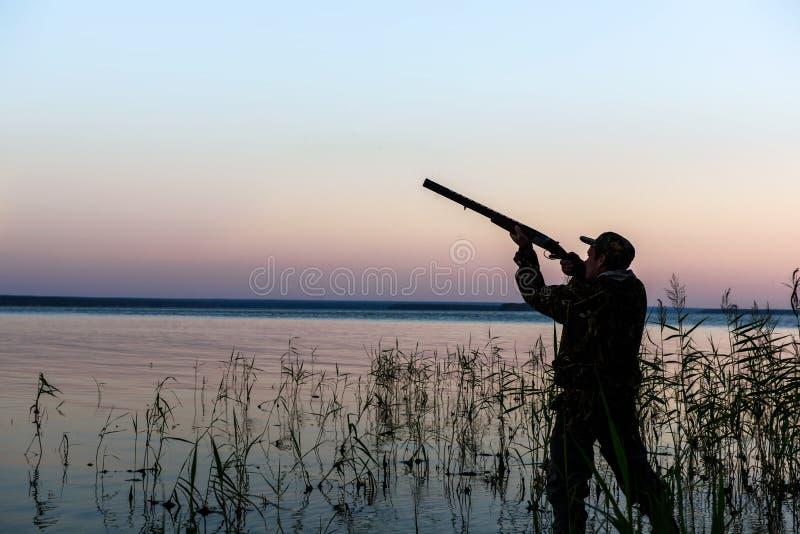 在日落的猎人剪影 免版税库存图片