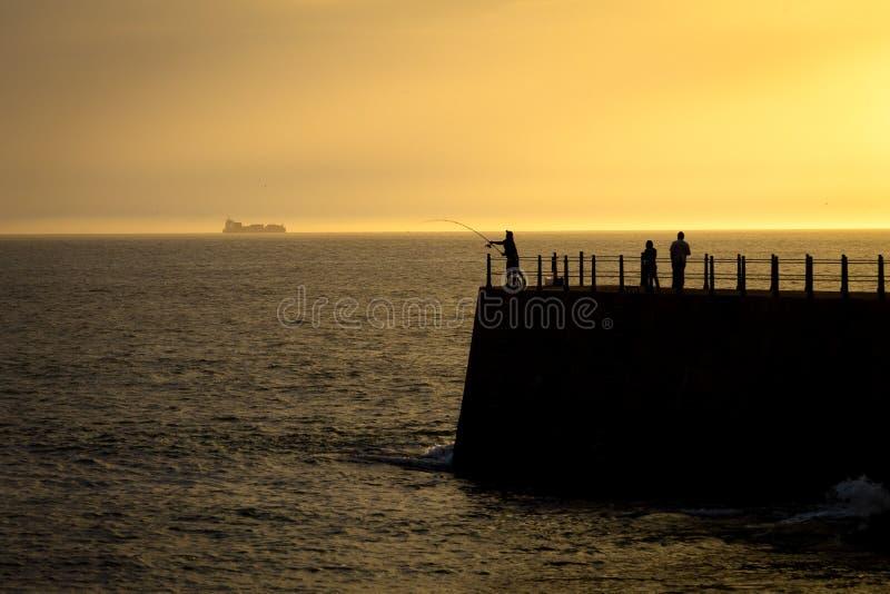 在日落的现出轮廓的码头 免版税库存图片