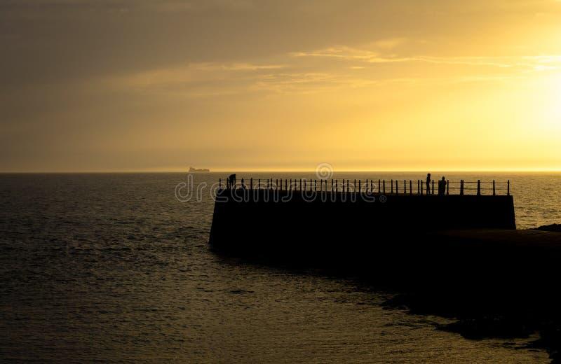 在日落的现出轮廓的码头 库存照片