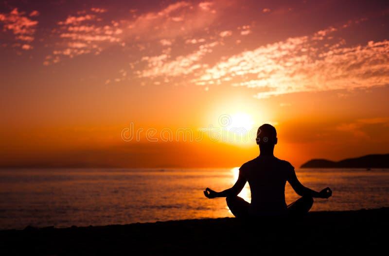在日落的瑜伽凝思 免版税图库摄影