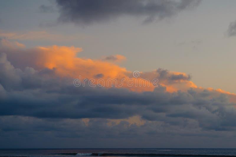 在日落的生动的橙色和灰色云彩在海洋 库存图片