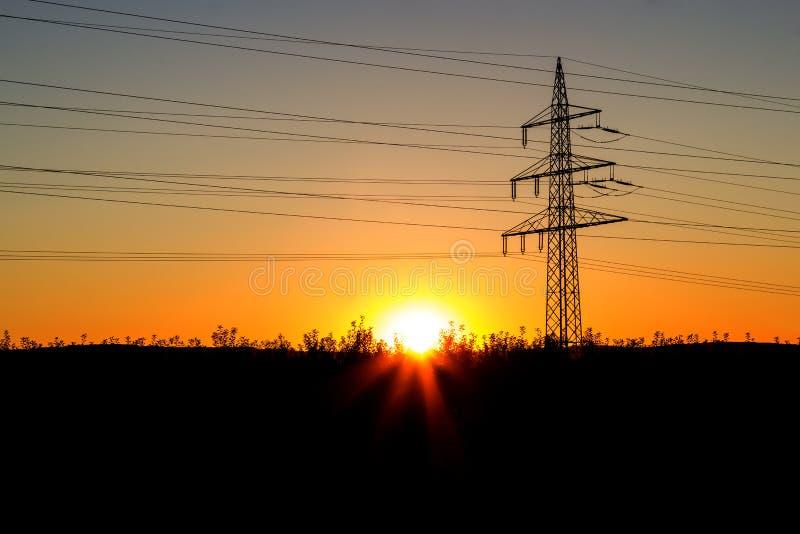 在日落的电定向塔 免版税库存图片