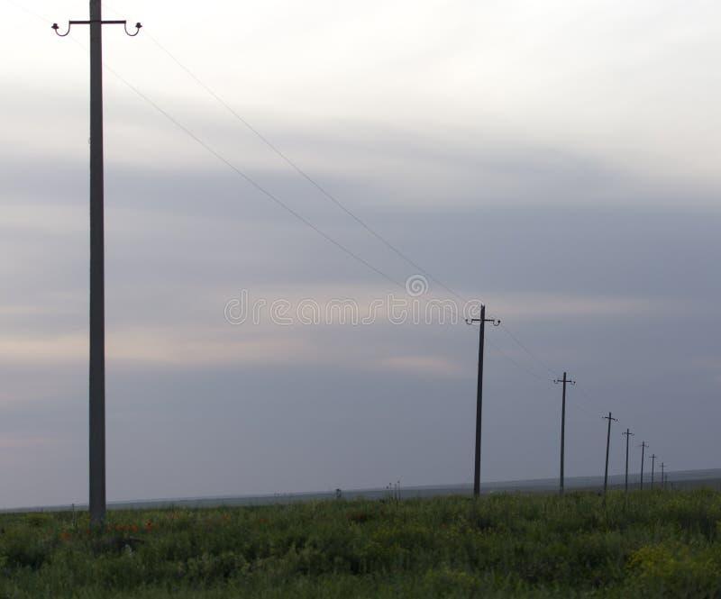 在日落的电源杆 免版税库存图片