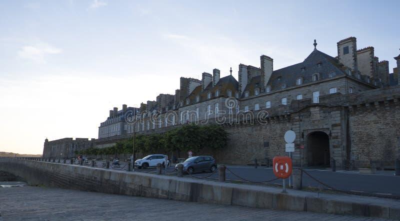 在日落的看法从老城市的墙壁有圣马洛湾花岗岩大厦的在布里坦尼,法国 免版税库存图片