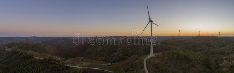 在日落的空中风力场涡轮剪影 清洗可再造能源电力发动的风车 免版税库存照片