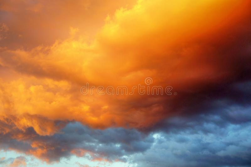 在日落的美丽的充满活力的剧烈的金黄多云天空 库存照片