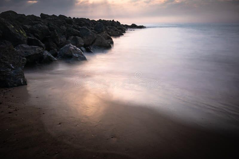在日落的美丽的含沙风景海滩,与在长的曝光的岩石防堤在巴斯克国家,法国,创造性的背景 库存照片