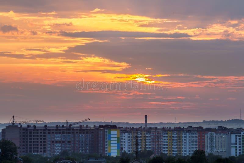 在日落的美丽的明亮的橙色天空在高公寓、工作塔吊和房子屋顶在绿色树中在dis 库存图片