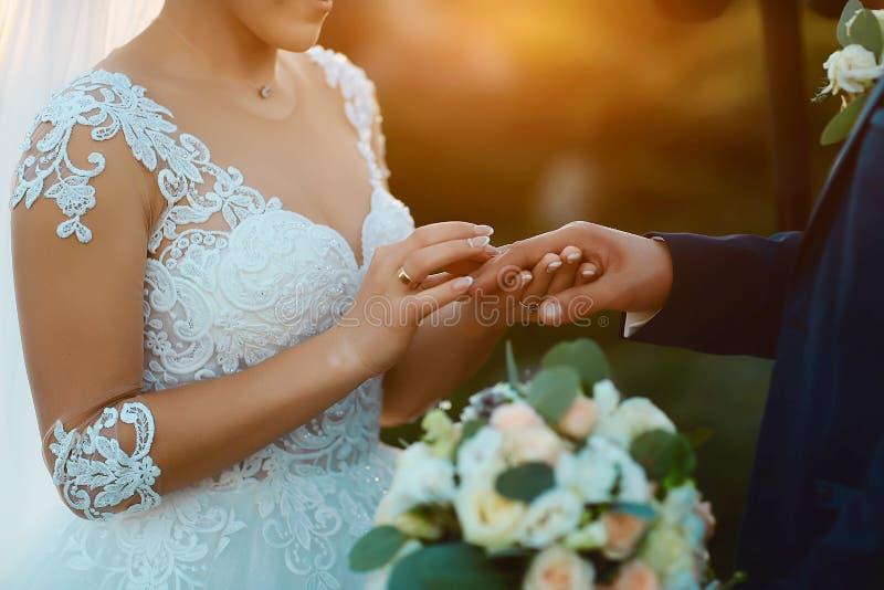 在日落的美好的婚姻的庆祝 一身白色庄重装束的一个新娘在她时髦握手并且投入圆环 库存图片