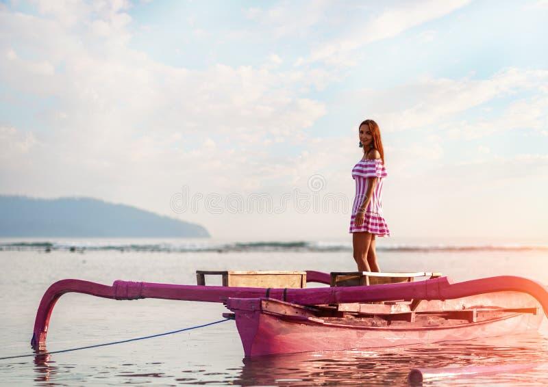 在日落的美好的少女身分在一艘小游船的海 反对海和天空 免版税库存图片