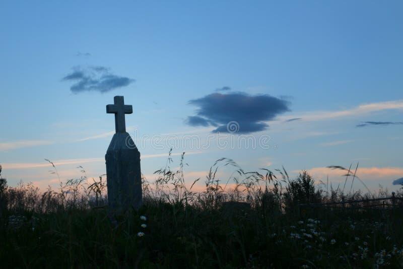 在日落的老发怒墓石剪影在公墓 免版税库存图片