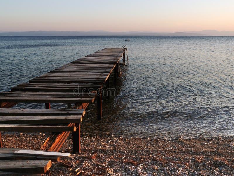 在日落的老打破的木码头 免版税库存图片