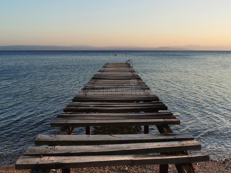 在日落的老打破的木码头 免版税库存照片