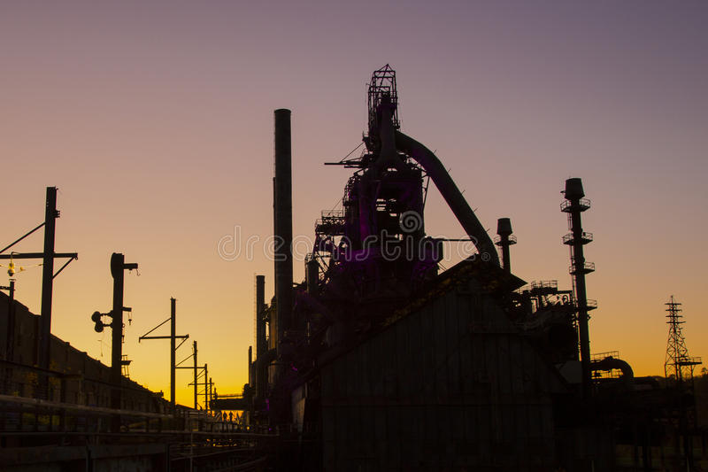 在日落的老钢铁厂剪影 免版税图库摄影