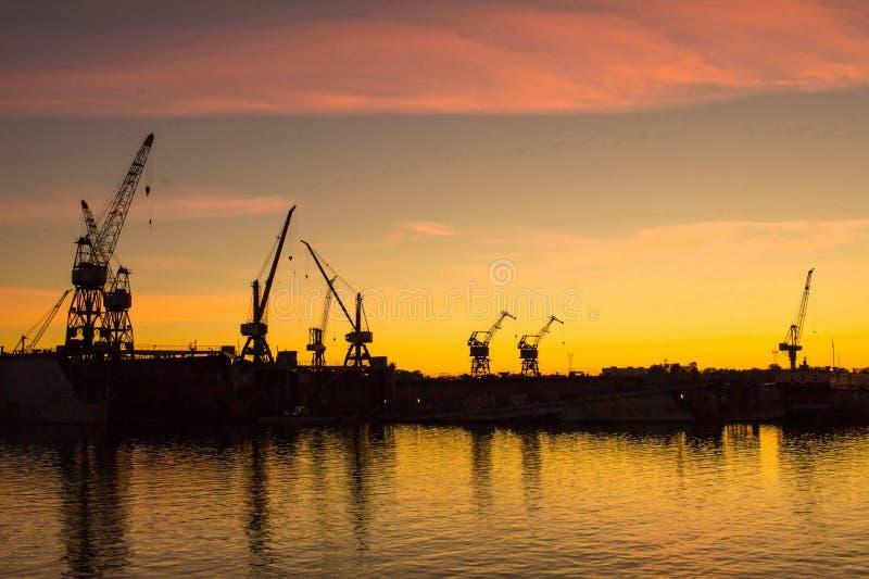 在日落的起重机在里加港  免版税库存图片