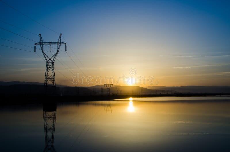 在日落的输电线 库存图片