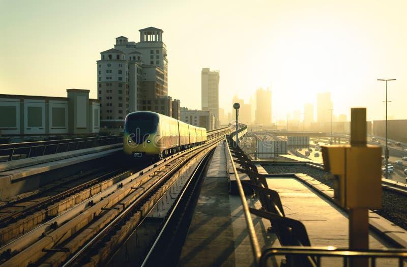 在日落的迪拜地铁 现代地铁、汽车通行在高速公路和企业大厦 城市街市地平线和铁路 免版税库存图片