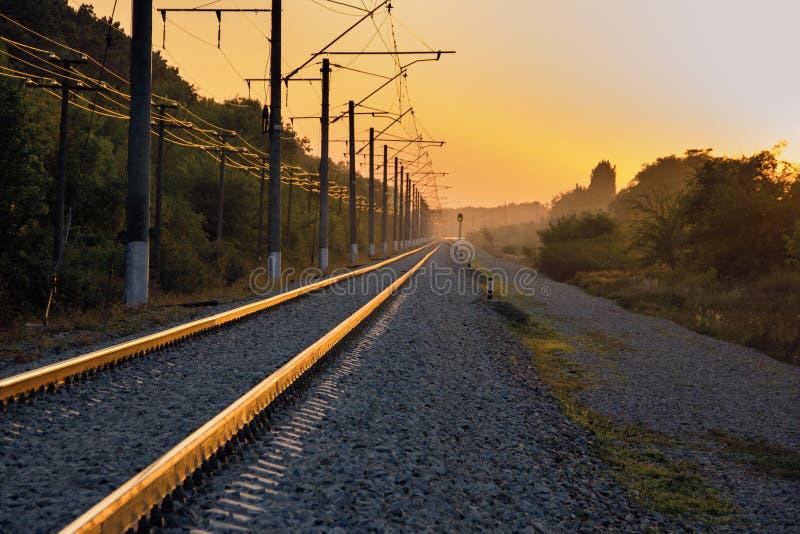 在日落的铁路和动臂信号机晚上 图库摄影