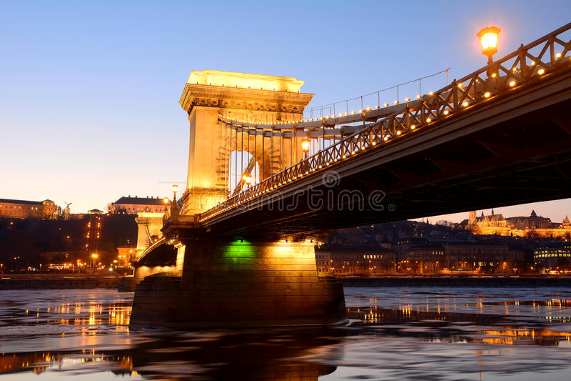 在日落的铁锁式桥梁在冰冷的多瑙河,布达佩斯, 库存照片